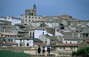 Three pilgrims at the entrance of Cirauqui with the village on the background