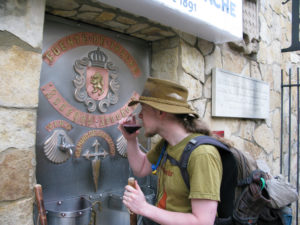 Pilgrim drinking a glass of wine at the fountain of Bodegas Irache doing the Saint James Way