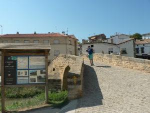 A pilgrim passing through a stone bridge in Lorca