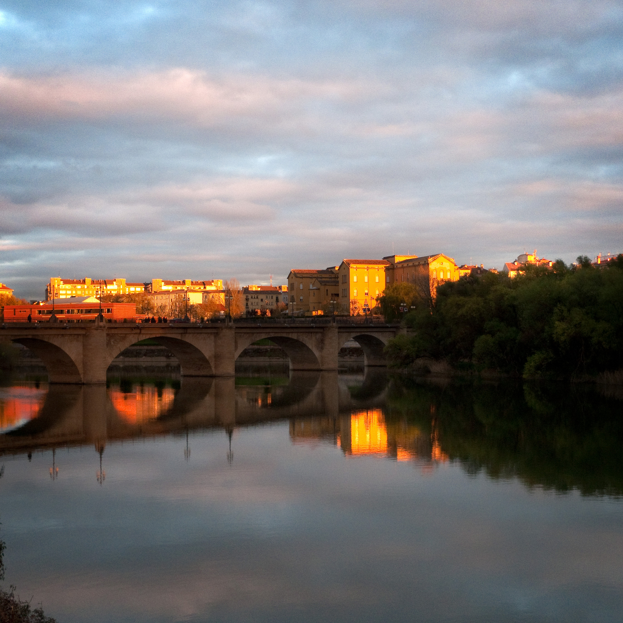 Logroño stone bridge over a river and during the sunset