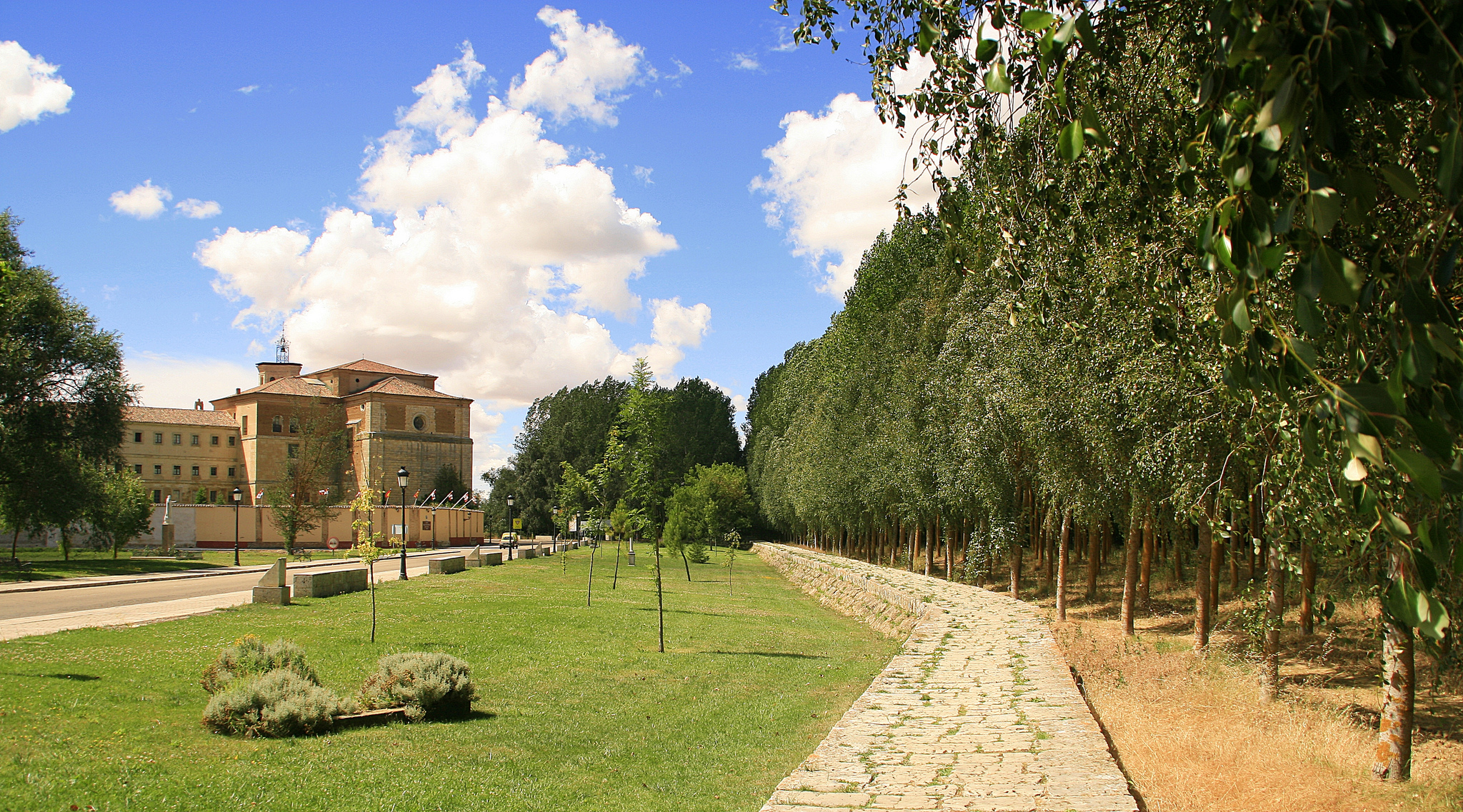 San Zoilo Monastery in the background during a sunny day surrounded by green trees