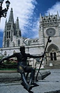 Statue of a pilgrim with the cathedral of Burgos in the background