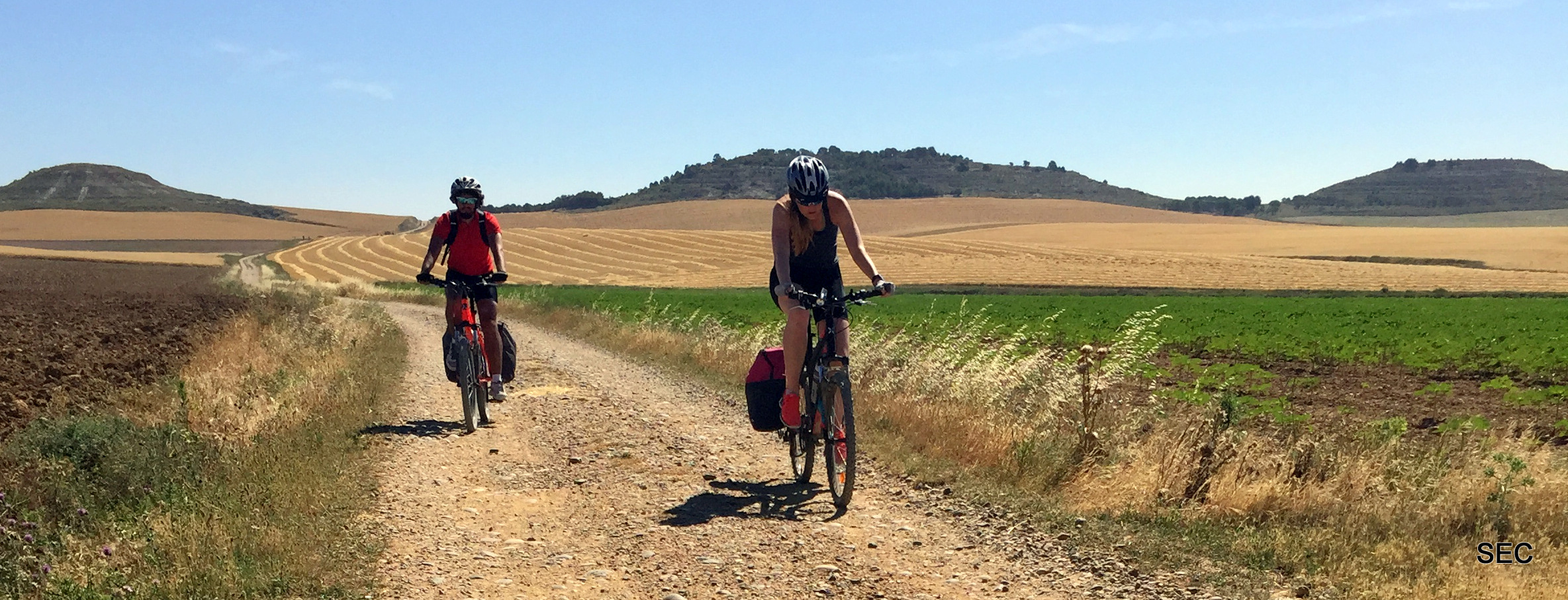 Two pilgrims doing the Saint James Way by bike on the road to Frómista