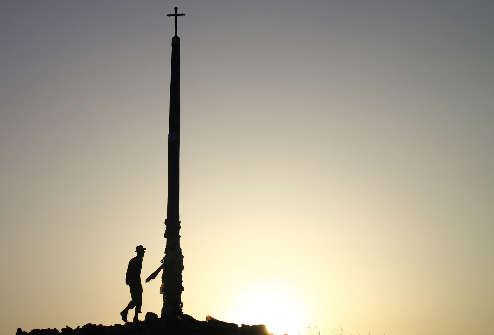 Pilgrim watching the sunrise from the Cruz de Ferro