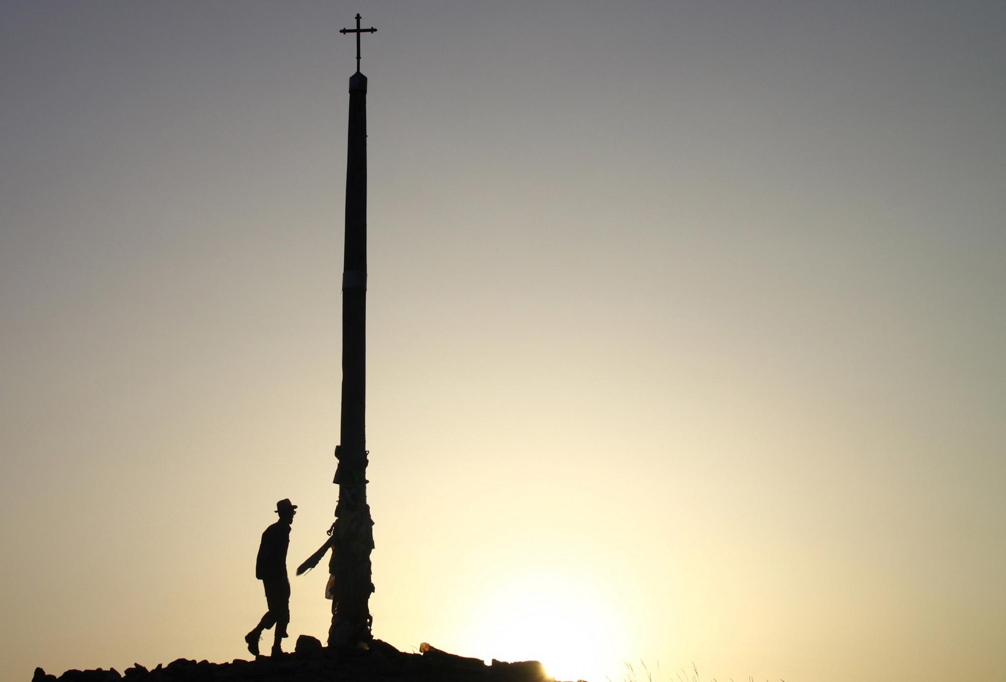 Pilgrim watching the sunrise from the Cruz de Ferro