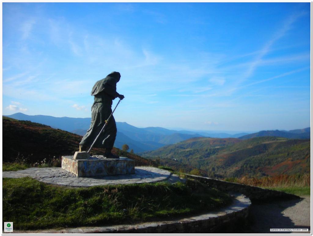 Estatua de un peregrino haciendo el Camino de Santiago en una montaña