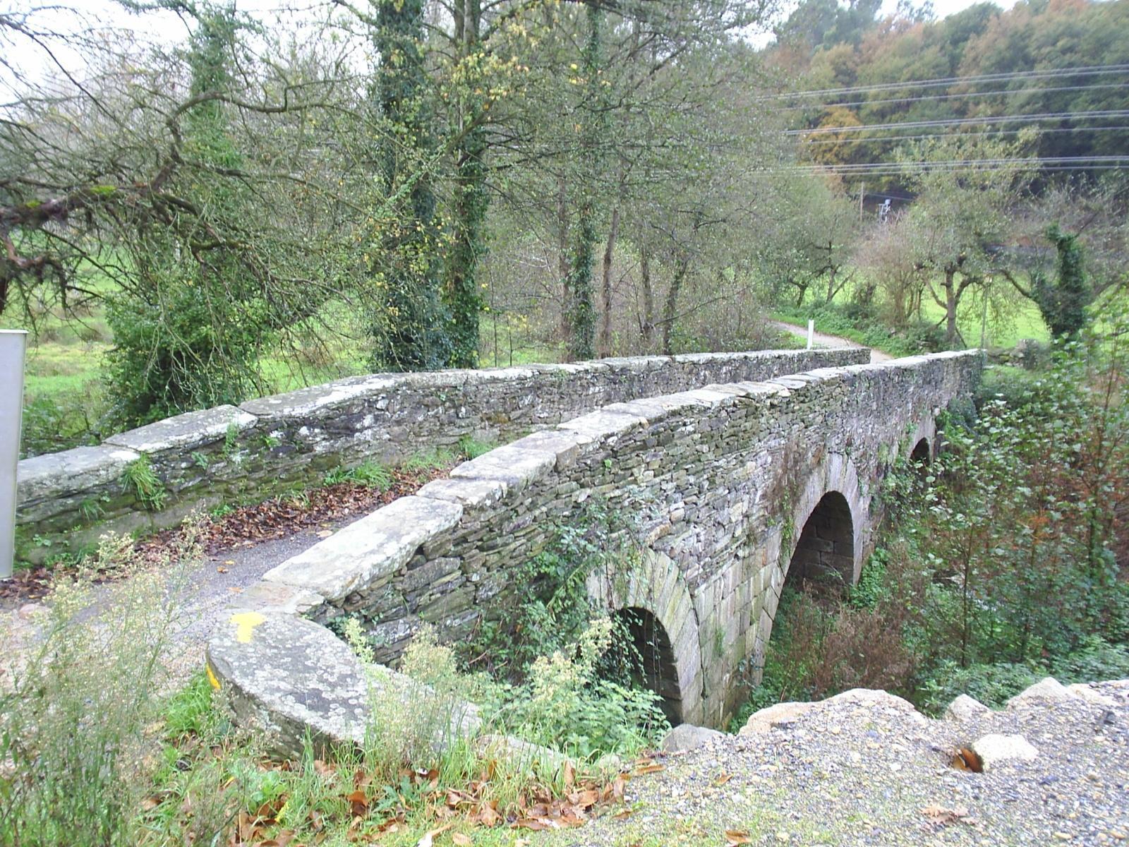 Puente de la Áspera hecho de piedra rodeado de monte