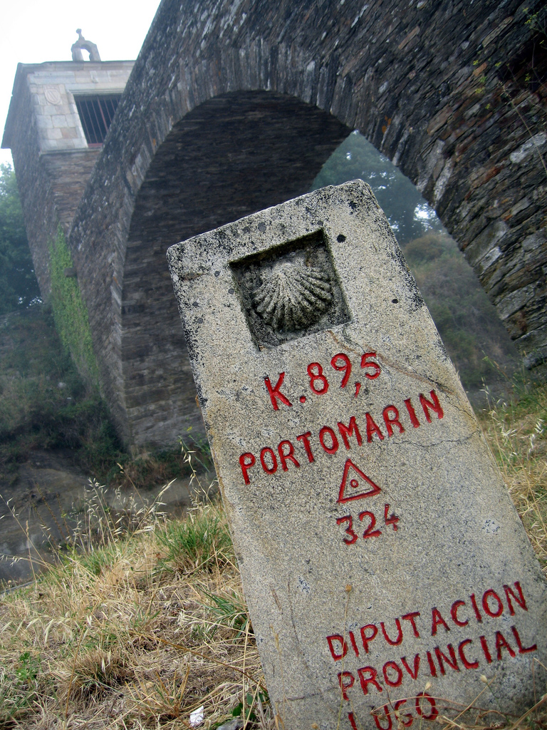 Milestone in Portomarín with a signal of the Saint James Way