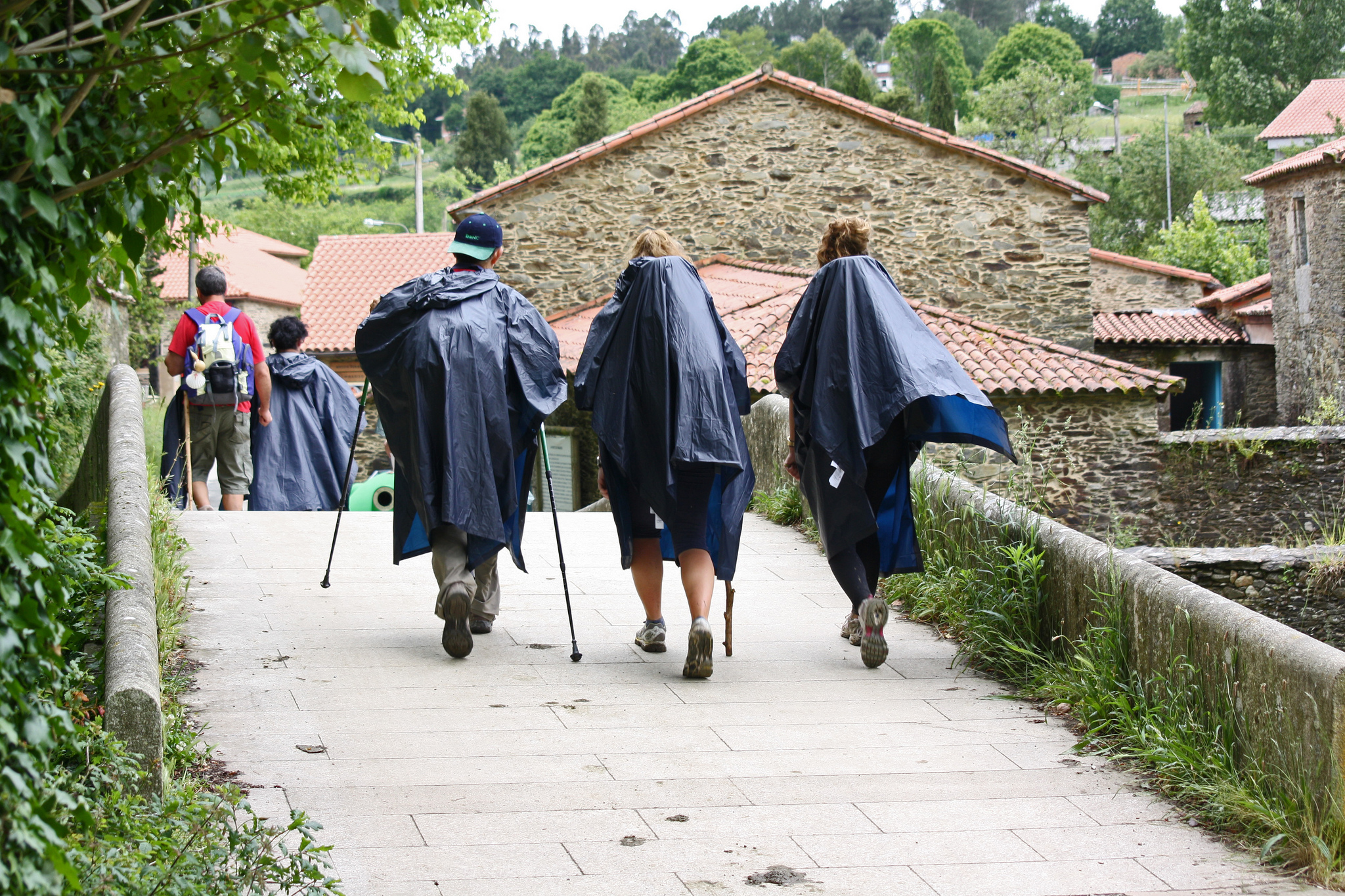 Pilgrims walking through a bridge in Ribadiso